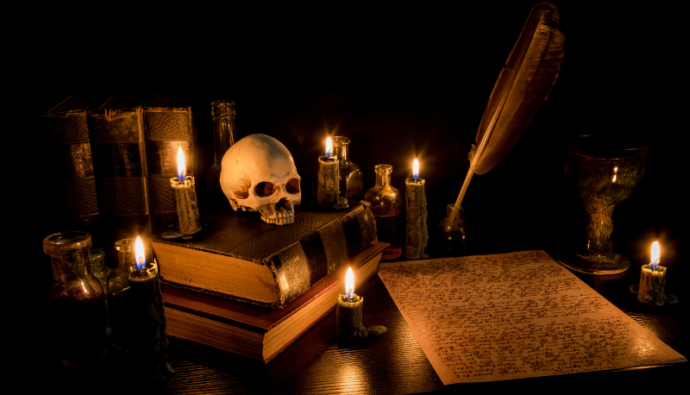books, parchment, pen, ink, skull